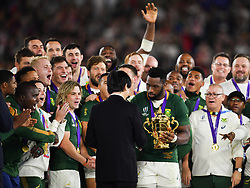 South Africa's Siya Kolisi is presented with the trophy by the Crown Prince of Japan after their 32-12 victory in the 2019 Rugby World Cup final match against England at Yokohama Stadium.
