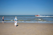 Strandgangers kijken naar de voorbijvarende reddingboot van de KNRM (Koninklijke Nederlandse ReddingMaatschappij) in Noordwijk aan Zee.<br />
