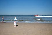 Strandgangers kijken naar de voorbijvarende reddingboot van de KNRM (Koninklijke Nederlandse ReddingMaatschappij) in Noordwijk aan Zee.<br /> <br /> People on the beach are watching at the lifeboat John Paul of the KNRM (Royal Dutch Rescue Organization) in Noordwijk aan Zee.
