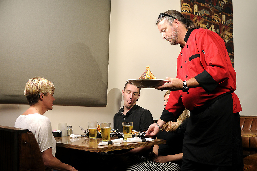Co-owner and chef Joel delivers a meal for friends at JJ's Restaurant and Sports Bar in Abingdon, VA on Monday, September 8, 2014. Copyright 2014 Jason Barnette