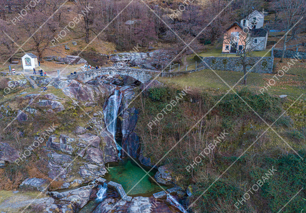 Romantic landscape of southern Switzerland, a waterfall of water a stone bridge and a green puddle. Very romantic