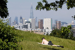 © Licensed to London News Pictures. 01406/2021. London, UK. A man sunbathes in Greenwich Park in South East London. Temperatures are expected to rise with highs of 28 degrees forecasted for parts of London and South East England today . Photo credit: George Cracknell Wright/LNP