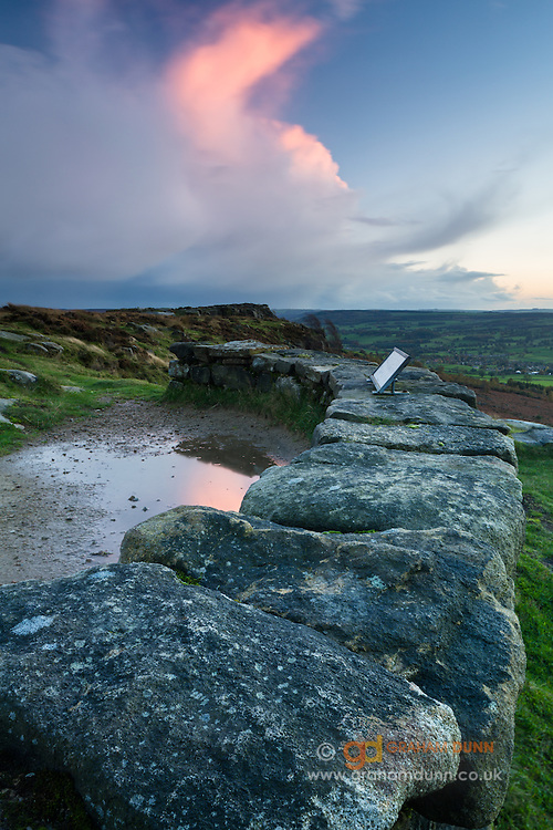 The curving wall of Baslow Edge's viewpoint at dusk, as it overlooks the Derwent Valley in the eastern flank of the Peak District National Park. Derbyshire, England, UK. October. Autumn.