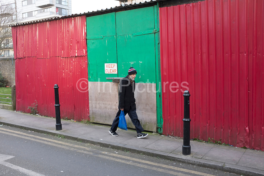 Bangladeshi man walking past red and green doors in Shadwell, East London, UK. This building is a store for food which is ebingb sold in local fruit and vegetable shops in the area.