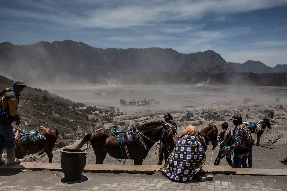 On a very dusty and windy day, the guides and their horses wait for their passengers at the ascent and steep climb to the crater on Mt. Bromo. September 10, 2018. East Java, Indonesia.