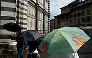 People passing by Florence's Duomo with umbrellas decorated with Renaissance paintings.