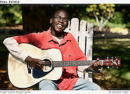 Young African American male playing a guitar.