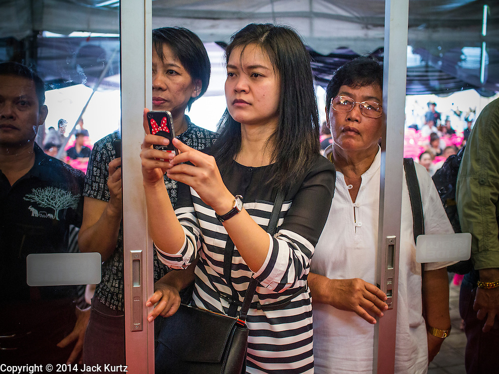 12 OCTOBER 2104 - BANG BUA THONG, NONTHABURI, THAILAND: Women watch the funeral rites for Apiwan Wiriyachai at Wat Bang Phai in Bang Bua Thong, a Bangkok suburb, Sunday. Apiwan was a prominent Red Shirt leader, member of the Pheu Thai Party of former Prime Minister Yingluck Shinawatra, and a member of the Thai parliament. The military government that deposed the elected government in May, 2014, charged Apiwan with Lese Majeste for allegedly insulting the Thai Monarchy. Rather than face the charges, Apiwan fled Thailand to the Philippines. He died of a lung infection in the Philippines on Oct. 6. The military government gave his family permission to bring him back to Thailand for the funeral. He will be cremated later in October. The first day of the funeral rites Sunday drew tens of thousands of Red Shirts and their supporters, in the first Red Shirt gathering since the coup.    PHOTO BY JACK KURTZ