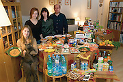 The Le Moine family in the living room of their apartment in the Paris suburb of Montreuil, with a week's worth of food. Michel Le Moine, 50, and Eve Le Moine, 50, stand behind their daughters, Delphine, 20 (standing), and Laetitia, 16 (holding spaghetti and Coppelius the cat). From the book Hungry Planet: What the World Eats (Model Released)
