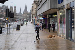 Edinburgh, Scotland, UK. 26 December 2020. Scenes from Edinburgh City Centre on a wet and windy Boxing Day during storm Bella. Today is first day that Scotland is under level 4 lockdown and all non essential shops and businesses are closed. As a result the streets are almost deserted with very few people venturing outside. Pic; Princes Street is almost deserted with all sops closed. Iain Masterton/Alamy Live News