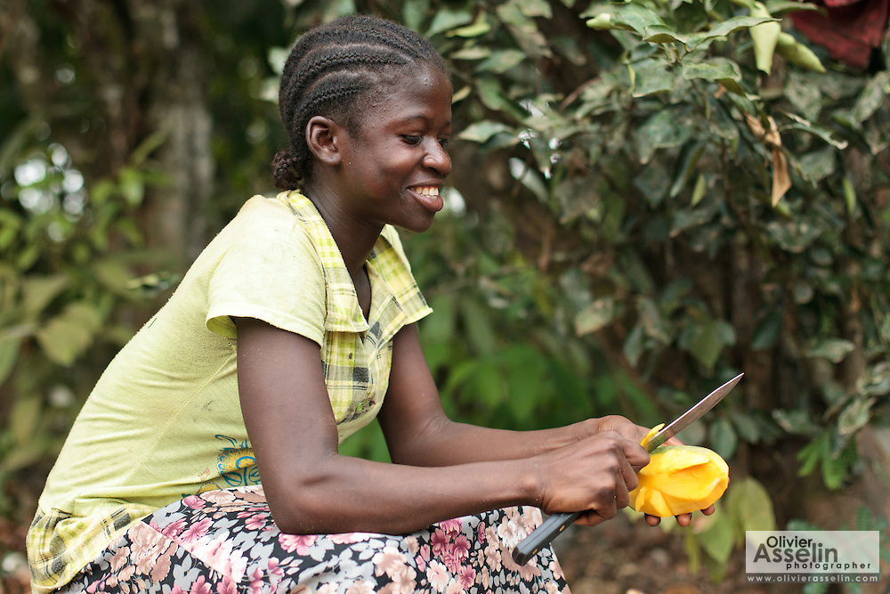 Baintu, 14, eats a mango outside her home in the village of Jenneh, Bomi county, Liberia on Tuesday April 3, 2012.