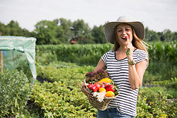Mid adult woman eating radish and carrying vegetable basket in community garden, Bavaria, Germany