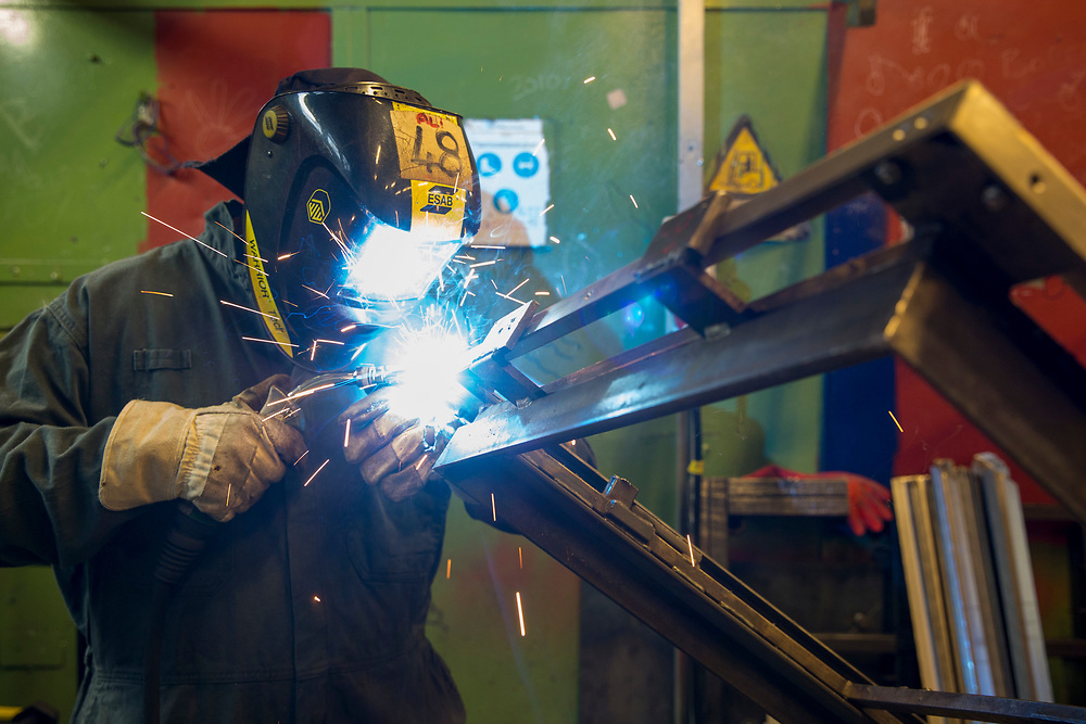 A prisoner welding a prison gate together inside the metal work training centre of the industries department at  HMP Featherstone, Wolverhampton, Staffordshire United Kingdom. HMP Featherstone is a Category C adult male training prison with a population of around 700 and operated by HM Prison Services. (Picture credit: © Andy Aitchison)