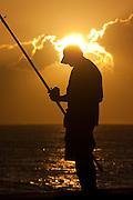 Lone fisherman at sunset in Hawaii