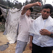One migrant cuts the hair of another at a migrant camp in the hills of northern San Diego, California where many live so they can save money and be close to the fields they work in. Please contact Todd Bigelow directly with your licensing requests. PLEASE CONTACT TODD BIGELOW DIRECTLY WITH YOUR LICENSING REQUEST. THANK YOU!
