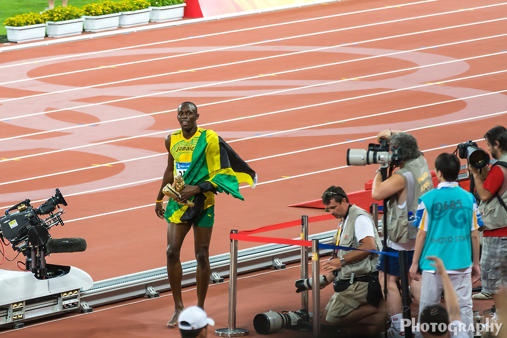 BEIJING, CHINA: Usain Bolt walking off track with his gold shoes after setting new world record