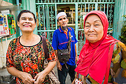 "10 JANUARY 2013 - BANGKOK, THAILAND: Buddhist and Muslim friends chat in front of a mosque in the Baan Krua neighborhood in Bangkok. The Ban Krua neighborhood of Bangkok is the oldest Muslim community in Bangkok. Ban Krua was originally settled by Cham Muslims from Cambodia and Vietnam who fought on the side of the Thai King Rama I. They were given a royal grant of land east of what was then the Thai capitol at the end of the 18th century in return for their military service. The Cham Muslims were originally weavers and what is known as ""Thai Silk"" was developed by the people in Ban Krua. Several families in the neighborhood still weave in their homes.   PHOTO BY JACK KURTZ"