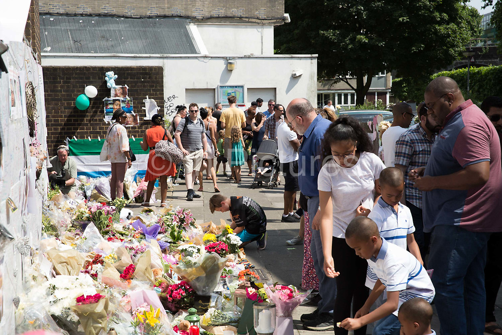 Flowers and candles line streets as people pay respect to the victims of Grenfell Tower on  in North Kensington, London, United Kingdom. The Grenfell Tower fire occurred on 14th June 2017 at the 24-storey block of public housing flats in North Kensington, West London. It caused at least 80 deaths and over 70 injuries, yet the actual numbers have yet to be confirmed