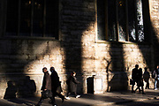 People pass by in reflected light in the City of London, England, United Kingdom.