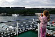 Child (5 years old) looking through pay-telescope at inter-island ferry. Near island of Korcula, Adriatic Sea, Croatia