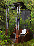 Outhouse with plywood covering chewed away by porcupines, Cowgill, Farmer, Terry Cabin, Upper Twin Lake, Lake Clark National Park, Alaska.