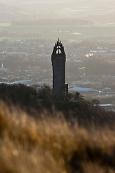 The Wallace Monument tower standing on the summit of Abbey Craig, a hilltop near Stirling in Scotland. View from the slope of the Dumyat, a hill at the western extremity of the Ochil Hills, in central Scotland..Pic © Michael Schofield....