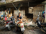 02 SEPTEMBER 2015 - BANGKOK, THAILAND: A man sits on the back of his motorscooter in Bang Chak Market. The Bang Chak Market serves the community around Sois 91-97 on Sukhumvit Road in the Bangkok suburbs. About half of the market has been torn down, vendors in the remaining part of the market said they expect to be evicted by the end of the year. The old market, and many of the small working class shophouses and apartments near the market are being being torn down. People who live in the area said condominiums are being built on the land.         PHOTO BY JACK KURTZ