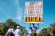 A man from the Los Angeles chapter of Bible Believers holds a banner as fans of Pope Francis leave following a short parade where Pope Francis was driven on the streets around the Ellipse, south of the White House in Washington, District of Columbia, U.S., on Wednesday, Sept. 23, 2015.