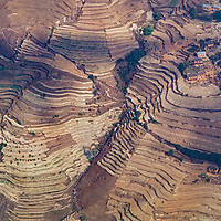 Terraced rice paddies surround a village in the foothills of Nepal.