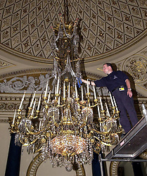 Technician Mark Boyd cleans the largest chandelier in the Music Room, Buckingham Palace, London. The Queen's chandeliers are being cleaned in preparation for next month's summer opening of the palace.  *  The largest chandeliers consist of thousands of prismatic lead-crystal drops and are around two metres tall. They weigh about three-quarters of a tonne and are illuminated by more than 100 light bulbs, connected by some 100 metres of wiring.