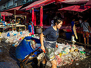 "04 DECEMBER 2018 - BANGKOK, THAILAND:  A worker hauls a barrel of trash past a pile of discarded plastic bags in Khlong Toei market. The issue of plastic waste became a public one in early June when a whale in Thai waters died after ingesting 18 pounds of plastic. In a recent report, Ocean Conservancy claimed that Thailand, China, Indonesia, the Philippines, and Vietnam were responsible for as much as 60 percent of the plastic waste in the world's oceans. Khlong Toey (also called Khlong Toei) Market is one of the largest ""wet markets"" in Thailand. December 4 was supposed to be a plastic free day in Bangkok but many market venders continued to use plastic.     PHOTO BY JACK KURTZ"