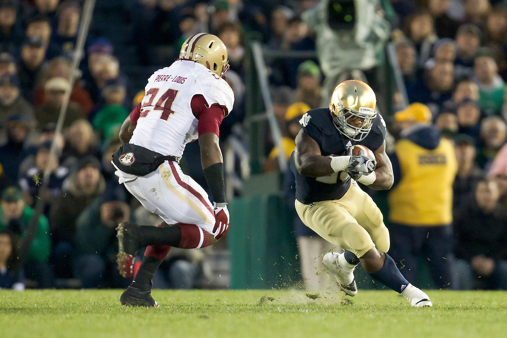 Notre Dame tailback Jonas Gray (#25) runs for yardage while Boston College linebacker Kevin Pierre-Louis (#24) pursues during second quarter of NCAA football game between Notre Dame and Boston College.  The Notre Dame Fighting Irish defeated the Boston College Eagles 16-14 in game at Notre Dame Stadium in South Bend, Indiana.