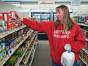 """25 FEBRUARY 2020 - BUTTERFIELD, MINNESOTA: CONNIE BRAATEN, who has lived in Butterfield since 2003, walks through the grocery section at the True Value Hardware Store in Butterfield. She used to shop in St. James, MN, about 10 miles away. Butterfield is a farming community of about 500 people 130 miles southwest of the Twin Cities. The town has been a """"food desert"""" for 10 years after its only grocery store closed in 2010. Barb Mathistad Warner and Mark Warner purchased the True Value store in Butterfield in December, 2018 and started selling groceries in the store in May, 2019. For residents of Butterfield going to a grocery store meant driving 10 miles to St. James, MN, or 20 miles to Windom, MN, the two nearest communities with grocery stores. The USDA defines rural food deserts as having at least 500 people in a census tract living 10 miles from a large grocery store or supermarket. There is a convenience store in Butterfield, but it sells mostly heavily processed, unhealthy snack foods that are high in fat, sugar, and salt.   PHOTO BY JACK KURTZ"""