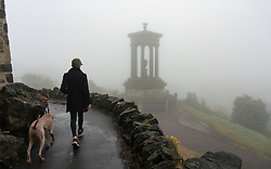 Edinburgh, Scotland, UK. 13 June 2020. A thick fog ,or haar as it is called locally, covers the city and obscures the famous tourist viewpoint from Calton Hill. Normally the viewpoint is busy with tourists , however, with the fog and Covid-19 lockdown continuing, only a few members of the public ventured up the hill today. The Dugald Stewart Monument is visible but not the famous Edinburgh skyline.  Iain Masterton/Alamy Live News