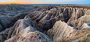 Panorama Point at sunrise. Erosion has exposed layers of ancient colorful sediments. Badlands National Park has the largest undisturbed mixed grass prairie in the United States. South Dakota, USA. This image was stitched from multiple overlapping photos.