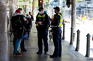 Police question two men during COVID-19 in Melbourne, Australia. Premier Daniel Andrews announced today that some minor changes will be made to the current Stage 4 Restrictions in Melbourne. As yet, there is no sign of any meaningful change despite numbers of new cases being under 5 for the 14 day rolling average. Zero cases and no deaths were recorded in the past 24 hours in Victoria. (Photo by Dave Hewison/Speed Media)