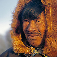 An elderly Inuit hunter relaxes, bathed in midnight sun.