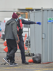 © Licensed to London News Pictures. 14/09/2021. Dover, UK. A Border Force officer assists a migrant at Dover Harbour in Kent. Migrants are continuing to attempt the crossing from France as the weather worsens. Photo credit: Stuart Brock/LNP