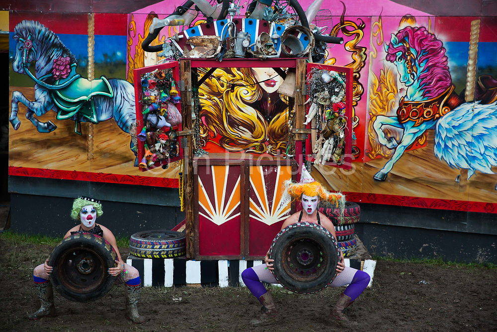 Clowns performing in the Unfairground, Glastonbury Festival 2016. Glastonbury Festival is the largest greenfield festival in the world, and is now attended by around 175,000 people. Its a five-day music festival that takes place near Pilton, Somerset, United Kingdom. In addition to contemporary music, the festival hosts dance, comedy, theatre, circus, cabaret, and other arts. Held at Worthy Farm in Pilton, leading pop and rock artists have headlined, alongside thousands of others appearing on smaller stages and performance areas.