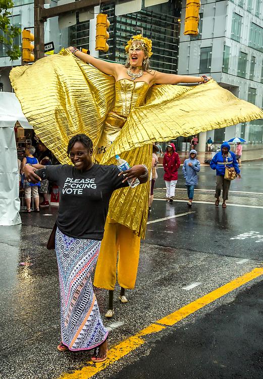 Big Whimsy stilt walker Nina Amaya with voting advocate on parade at Artscape, Baltimore arts festival,