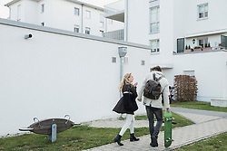Young couple walking with skateboard on street, Munich, Bavaria, Germany