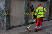 A street sweeper with contractor Amey brushes round a leaning automatic traffic control bollard in St . Swithins Lane, City of London.