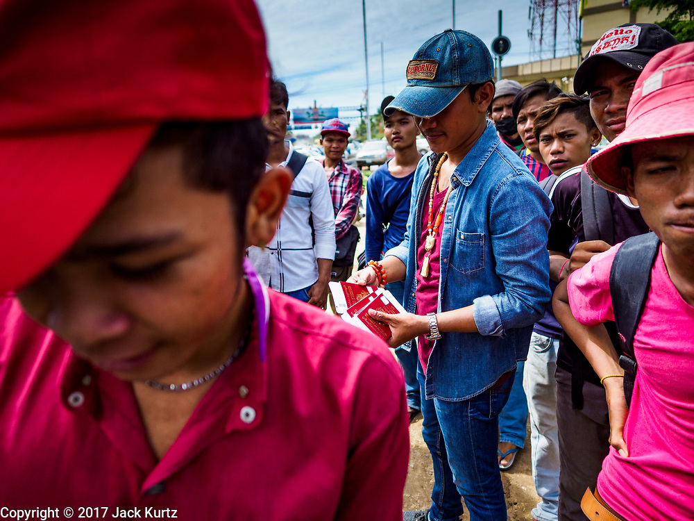 05 JULY 2017 - POIPET, CAMBODIA: A man who works for a labor broker in Poipet (blue hat) gives Cambodian migrant workers he is accompanying to Thailand their passports and paperwork. The Thai government proposed new rules for foreign workers recently. The new rules include fines of between 400,000 and 800,00 Thai Baht ($12,000 - $24,000 US) and jail sentences of up to five years for illegal workers and people who hire illegal workers. Hundreds of companies fired their Cambodian and Burmese workers and tens of thousands of workers left Thailand to return to their countries of origin. Employers and human rights activists complained about the severity of the punishment and sudden implementation of the rules. On Tuesday, 4 July, the Thai government suspended the new rules for 180 days and the Cambodian and Myanmar governments urged their citizens to stay in Thailand, but the exodus of workers continued through Wednesday.     PHOTO BY JACK KURTZ