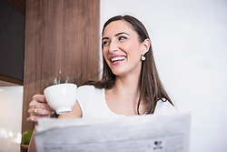 Woman drinking a cup of coffee and reading a newspaper, Munich, Bavaria, Germany