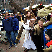 """While visitors pose for photographs with a Santa Claus dinosaur,  Michael Grant, 28, """"Philly Jesus,"""" walks through the Christmas Village in LOVE Park towards the nativity scene after carrying this 12 foot cross 8 miles through North Philadelphia to Center City as part of a Christmas walk to spread the true message of the holiday in Philadelphia, PA on December 20, 2014.  As many as a half dozen others joined him for numerous miles as he trekked southward down Broad Street.  Some shouted """"Praise Jesus!"""" and """"Thank you for doing this!""""at the sight.  Nearly everyday for the last 8 months, Grant has dressed as Jesus Christ, and walked the streets of Philadelphia to share the Christian gospel by example.  He quickly acquired the nickname of """"Philly Jesus,"""" which he has gone by ever since."""