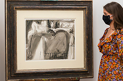 "© Licensed to London News Pictures. 01/09/2020. LONDON, UK. A staff member poses with ""Le Voyeur"", 1 August 1933,  by Pablo Picasso.  Preview of ""Atelier Picasso"", a new exhibition recreating Pablo Picasso's studio in Cannes featuring his drawings, prints, ceramics and furniture.  The show is at Bastian gallery in Mayfair 3 September to 31 October 2020.  Visitors will be required to wear a facemask and practice social distancing.  Photo credit: Stephen Chung/LNP"
