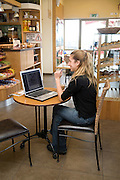 Young female student in her 20s working on her laptop in a cafe utilizing the wireless connection to the web