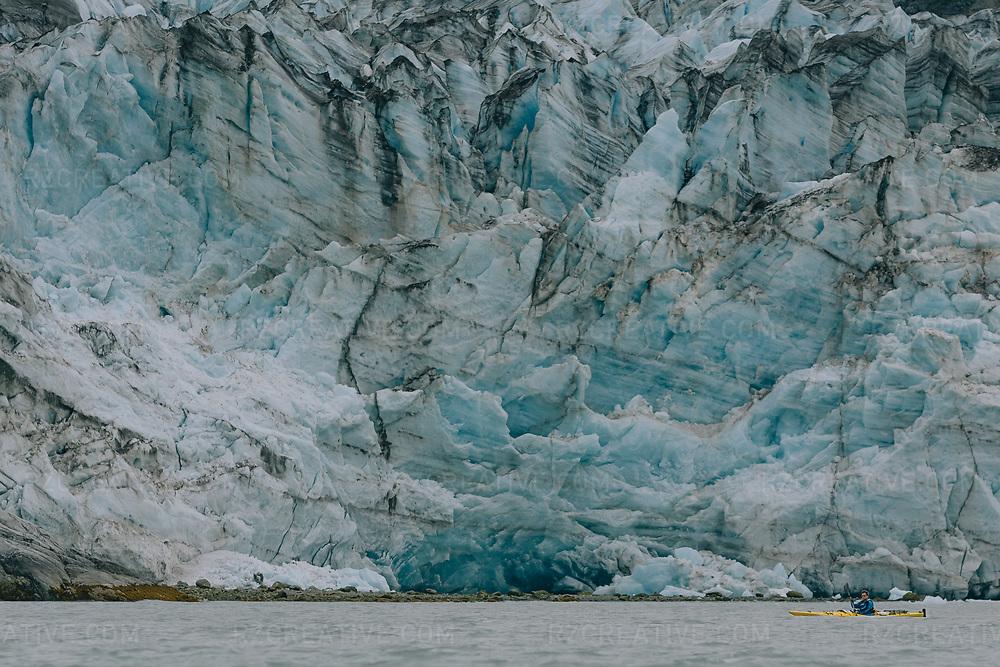 Kayaker paddling near Lamplugh Glacier in the West Arm of southeast Alaska's Glacier Bay National Park. Photo © Robert Zaleski / rzcreative.com
