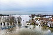 Nederland, Nijmegen, 19-12-2017Het waterpeil van de rivier de Waal. Vandaag bereikte de huidige golf haar hoogste punt, maar dat is nog ver beneden een alarmerende stand. Het voetgangersbruggetje, wandelbrug de Ooijpoort dat Nijmegen verbindt met de stadswaard in de Ooijpolder is niet meer te gebruiken en de uiterwaarden lopen onder tot aan de dijk. Het vee is naar hoger land gedreven. Foto: Flip Franssen