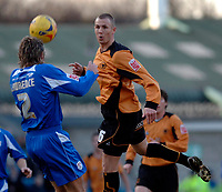 Photo: Daniel Hambury.<br />Millwall FC v Wolverhampton Wanderers. Coca Cola Championship. 21/01/2006.<br />Millwall's Matt Lawrence (L) and Wolves' Kenny Miller go for a header.